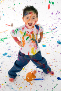 Adorable 3 year old boy covered in bright paint.